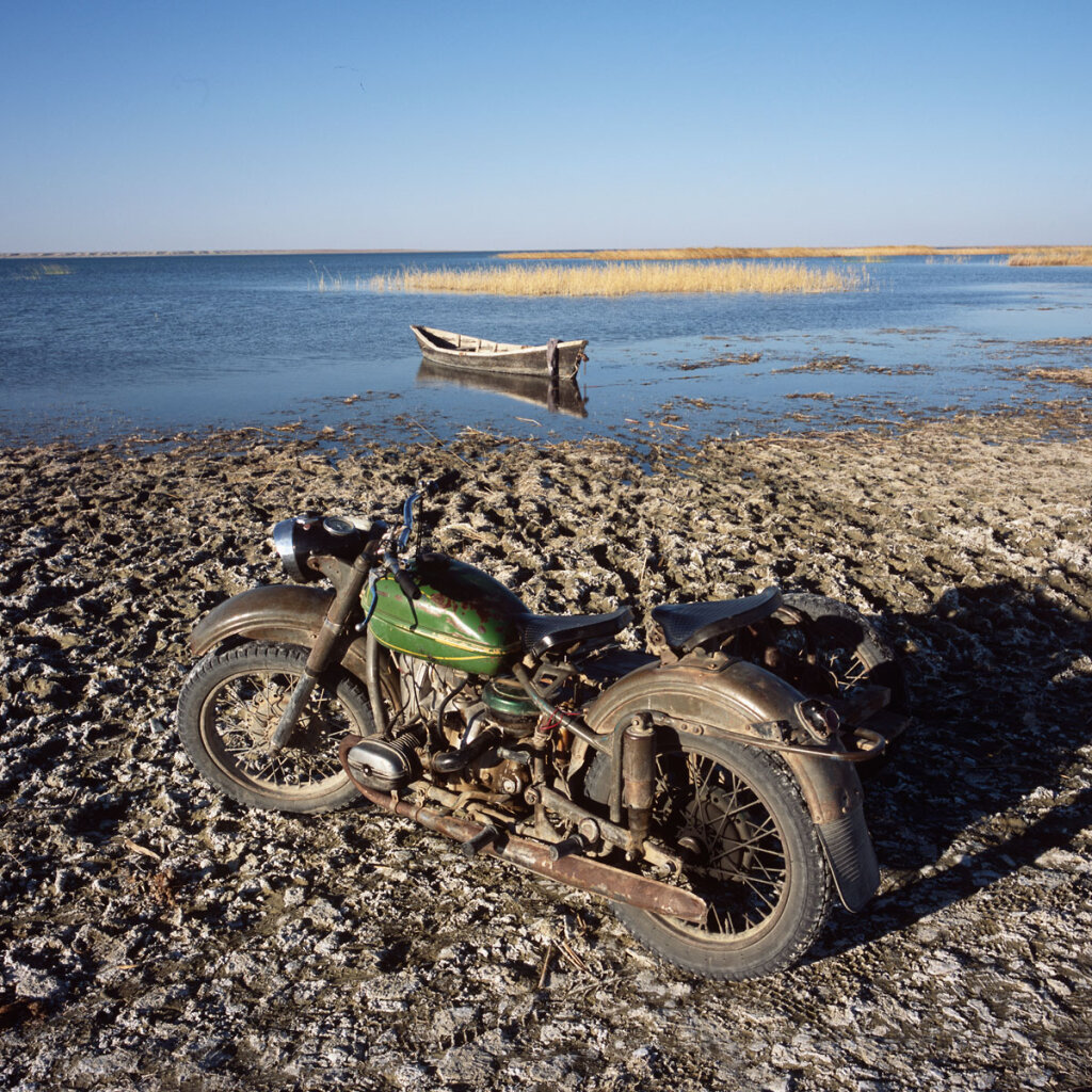 A motorcycle belonging to a fisherman is parked in front of the  Kambash Lake