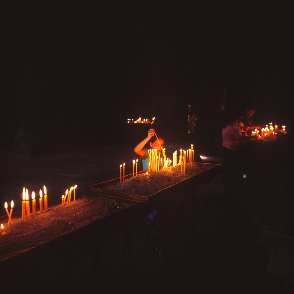 Child lighting candles in Geghard Monastery